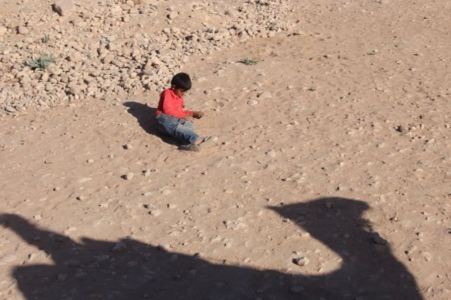 A boy plays in the dirt while my camel passes by
